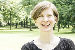 Betty Wollgarten steht in einem Park und lächelt in die Kamera